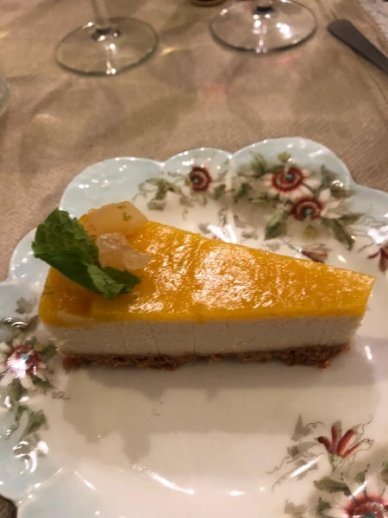 A guest's picture of their cheesecake, garnished with candied ginger, lime zest, and mint