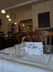 Tables set with hand-drawn place cards and vintage cutlery